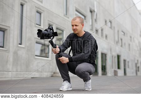 Videography, Filmmaking And Creativity Concept - Professional Male Videographer Shooting Video Using