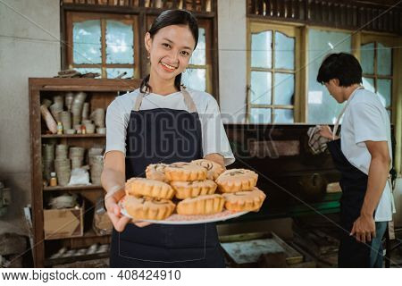 Smiling Girl Making A Cake Wearing An Apron Carrying A Plate Of Cake
