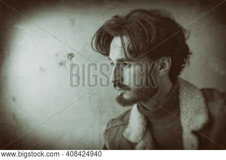 Men's beauty and hairstyle. Black-and-white portrait of a handsome man with wavy dark hair and a beard wearing jeans jacket. Copy space. Denim style.