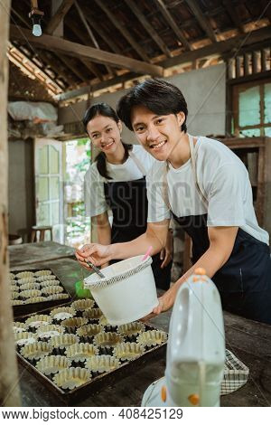 Smiling Asian Man Wearing Apron Looking At The Camera While Pouring The Cake Batter On The Cake Tin