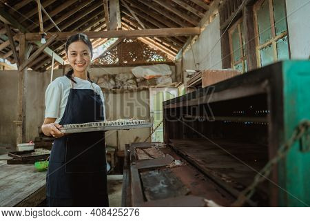 A Girl Wearing An Apron Smiles At The Camera As She Brings A Baking Sheet Filled With Cookie Dough