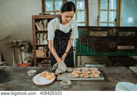 Asian Woman Wearing An Apron Using A Cloth Rag Takes A Hot Mini Cake Mold That Has Just Been Baked B
