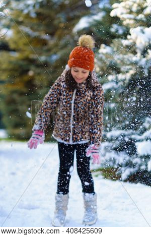 child girl throws up snow and playing in the winter forest, bright snowy fir trees, beautiful nature. Blur Image