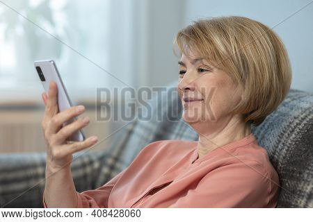 Happy Positive Woman, Elderly Senior Mature Lady Is Looking At Screen Of Her Cell Mobile Phone And S