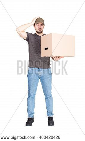 Confused Delivery Man, Full Length Portrait, Holding A Cardboard Box While Keeps A Hand To Head, Iso