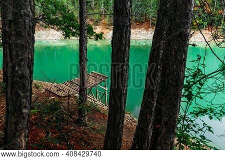 Forest Lake With Wooden Pier. Beautiful Turquoise Lake With A Wooden Pier In A Coniferous Forest. Em