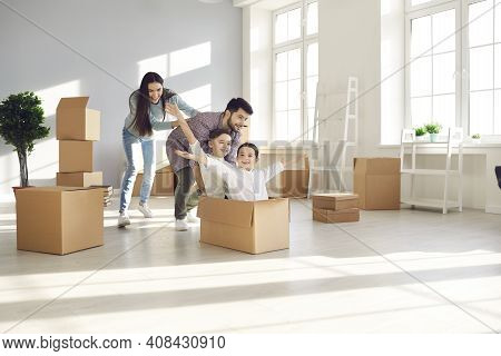 Happy Family Having Fun And Playing With Cardboard Boxes In Their Newly Bought House