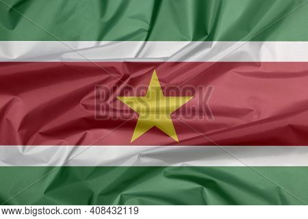 Fabric Flag Of Suriname. Crease Of Surinamer Flag Background, Green And Red With Large White Border