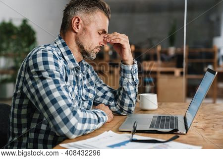 Unhappy grey man with headache working with laptop while sitting in office