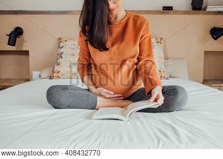 Front View Of Cropped Long Hair Brunet Caucasian Pregnant Woman, Sitting In Crossed Legs In Bed, Rea