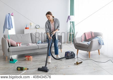 Unhappy Young Woman Vacuuming Messy Apartment After Party, Cleaning Up Chaos After Holiday Celebrati