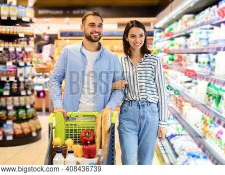 Happy Millennial Family Couple Buying Food In Supermarket, Choosing Products Walking With Cart Along