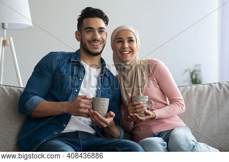 Happy Middle-eastern Couple Sitting On Couch At Home, Drinking Tea, Watching Movie Together, Copy Sp