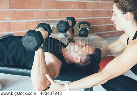 Fit Man Is Doing Dumbbell Exercises At Gym While A Female Instructor Is Helping Him On A Gym Routine
