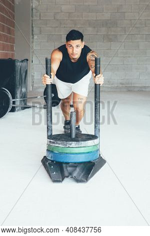 Fit Muscular Young Man Is Pushing Weight On A Cross Fit Routine At Gym. Sled Pushing Exercise. Worko