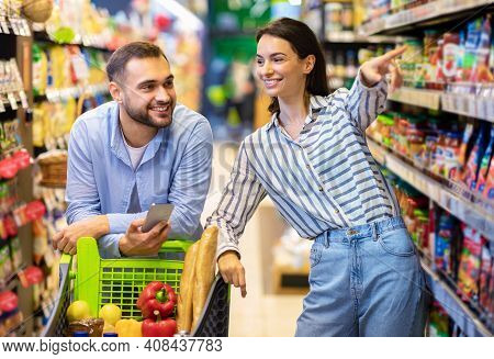 I Want This. Millennial Couple Doing Grocery Shopping Together, Man Leaning On Cart And Using Mobile