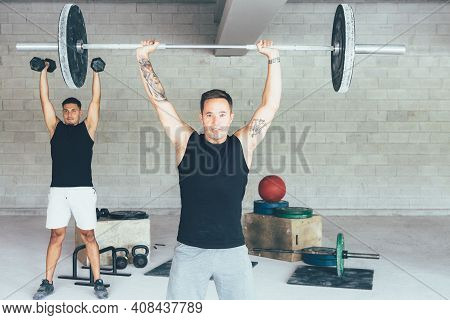Front View Of A Pair Of Young Fit Men Doing Barbell Jerks And Dumbbell Exercises At The Gym. Fitness
