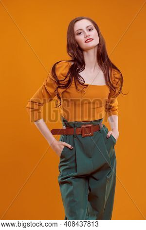 Bright elegant female clothes. Portrait of a beautiful smiling girl in colorful clothes on orange background. Fashion shot.