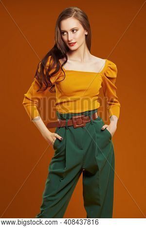 Portrait of a beautiful fashionable young woman in colorful clothes on dark orange background. Fashion shot. Bright colors in clothing.