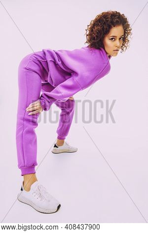 Aattractive young girl model posing in a bright sportswear and sneakers on a white background. Sportswear fashion. Studio shot.