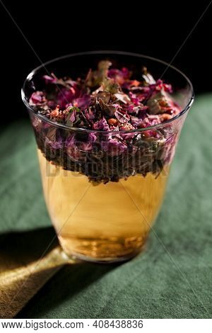 A Glass With Floral And Herb Infused Water On Green Background Close-up. Home Remedy Concept