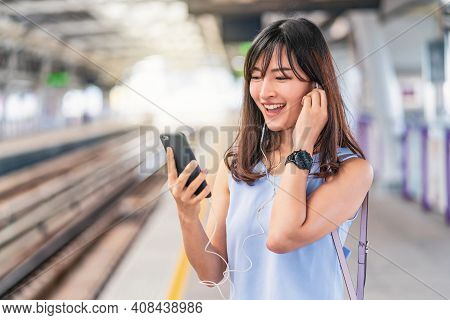 Young Asian Woman Passenger Listening Music Via Smart Mobile Phone In Subway Train When Traveling In