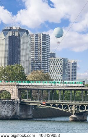 Subway Train On The Bridge Over Seine River Against Skyscrapers With Air Balloon In Paris, France