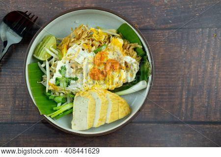 Stir Fried Noodles Or Pad Mee Korat Served With Fried Vietnamese Pork Sausage On Wood Table