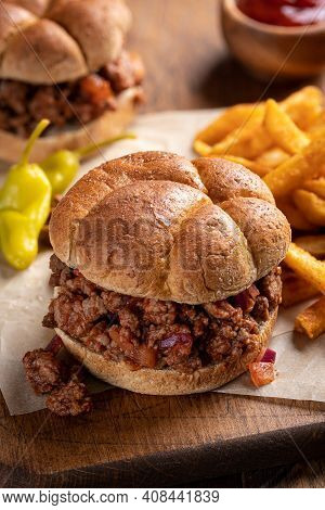 Sloppy Joe Sandwiches And French Fries On A Wooden Cutting Board