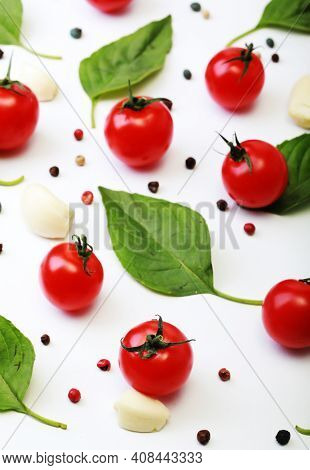Tomato, basil, spices, pepper, garlic. Vegan diet food, creative cherry tomato composition isolated on white. Fresh basil, herb, tomatoes, cooking concept, top view.