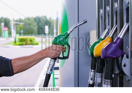 Man Holds A Refueling Gun In His Hand For Refueling Cars. Gas Station With Diesel And Gasoline Fuel