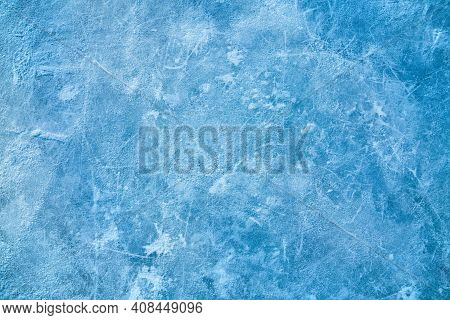 Ice Blue Background With Ice Skating Tracks. Covered With A Thin Layer Of Snow. Rink. Frozen Water,