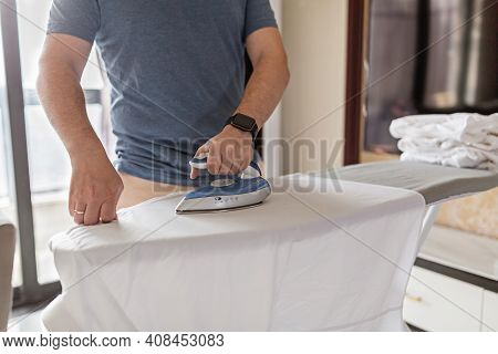 Young Caucasian Man Dressed In Blue T Shirt, Irons Shirt On Ironing Board, Takes Care Of Clothes, Do