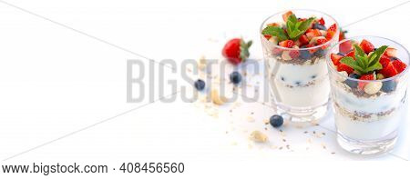 Banner. Two Glasses Of Strawberry Parfait Made With Fresh Fruit, Yogurt, Blueberries, Flax Seeds And