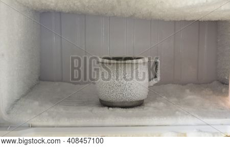 Stainless Steel Drinking Water Glass In Freezer Of A Refrigerator. Ice Buildup Inside Of A Freezer W