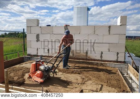 Vibrating Plate In Use, The Worker With The Help Of A Vibrating Plate Compacts The Sand, Building A
