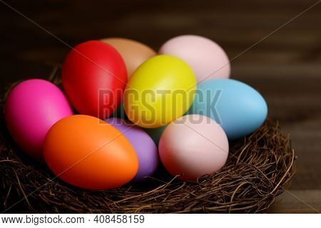 Multi Colored Easter Eggs In Birds Nest On Dark Wooden Planks Table Closeup View Selective Focus. Ea