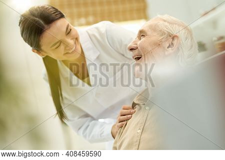 Friendly Medic Smiling At The Senior Citizen In Her Care