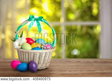 Wicker Basket With Bright Painted Easter Eggs On Wooden Table, Space For Text