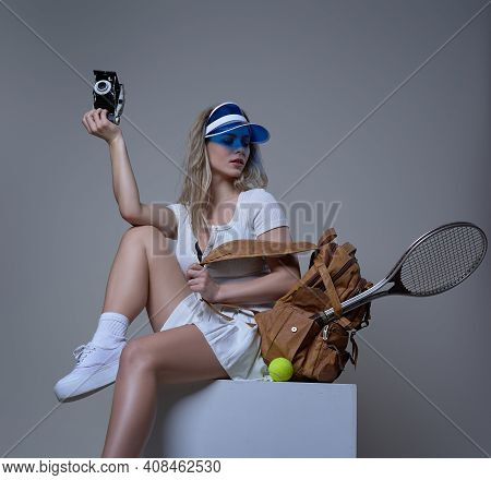 Young Female Tennis Player Sits On Box Holding Photocamera And Backpack With Racquet And Tennis Ball