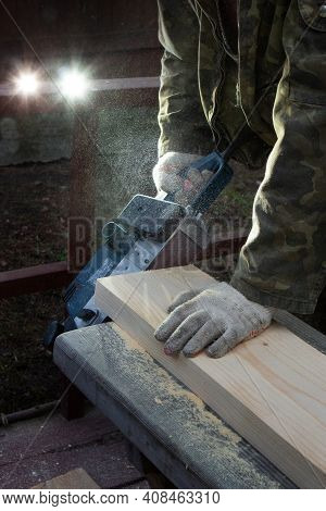 Hands Of A Joiner With A Grinder Machine. Flying Shavings, Wooden Board. The Work Of A Professional.