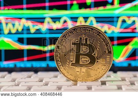 Close Up Photo Of Golden Bitcoin Standing On White Keyboard With Colorful Graphs On On Monitor Scree