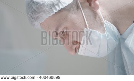 Close-up Of Masked Surgeon During Surgery. Action. Young Professional Surgeon In Mask Looks Down. Su