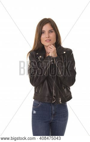 Girl With Anxiety On Her Face Stands With Folded Hands And Worry. Woman In The Leather Jacket Is Ver