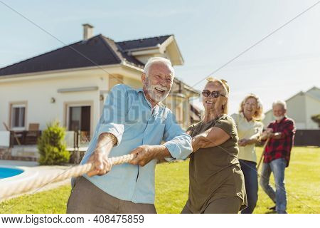 Senior People Having Fun Playing Tug Of War Game, Spending Sunny Summer Day Outdoors; Group Of Elder