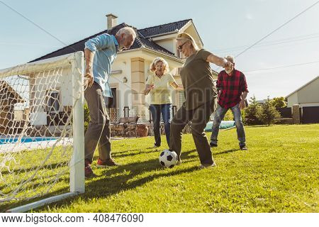 Group Of Active Elderly People Having Fun Playing Football On The Lawn In The Backyard, Enjoying Sun