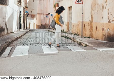 Brunet Caucasian Pregnant Woman Walking On The Streets Of An Old City And Crossing A Crosswalk. Fash