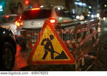 Road Works Ahead Sign At Winter Night Street Near Pit