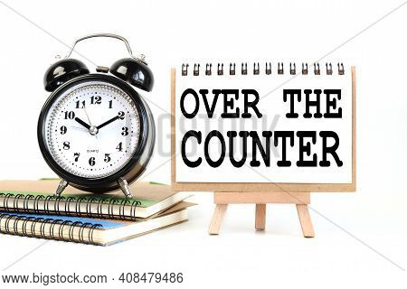 Otc - Over The Counter. Text On White Notepad Paper On A Stand Next To Our Desk Clock On A Sideboard