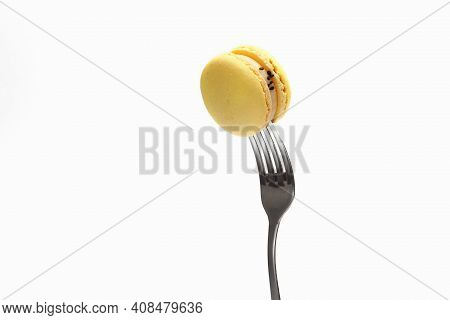 Yellow Macaroons On A Fork, Top View. Sweet French Macaroons Cake Isolated On White Background
